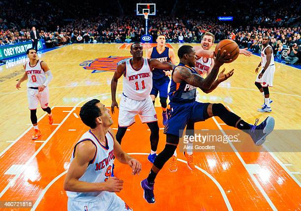 Eric Bledsoe of the Phoenix Suns attempts to pass around Travis Wear of the New York Knicks in the second half at Madison Square Garden on December...