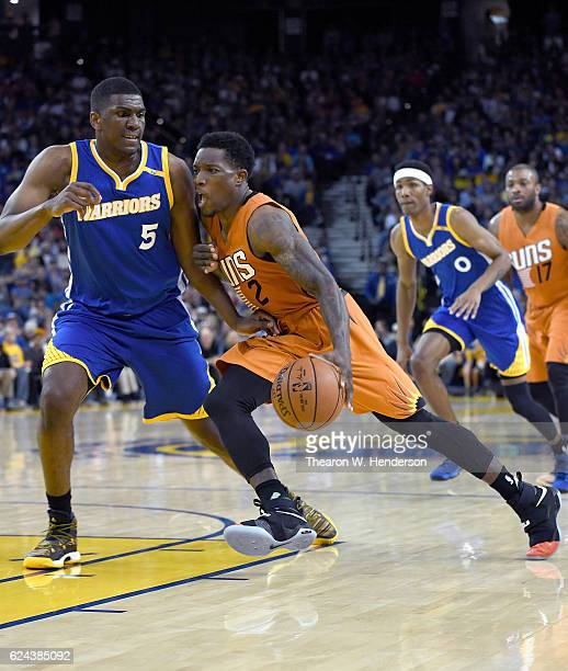 Eric Bledsoe of the Phoenix Suns drives towards the basket with the ball on Kevon Looney of the Golden State Warriors during an NBA basketball game...