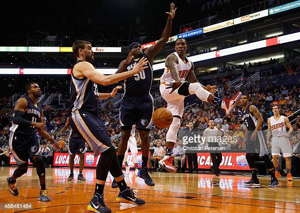 Eric Bledsoe of the Phoenix Suns passes the ball around Zach Randolph and Marc Gasol of the Memphis Grizzlies during the first half of the NBA game...