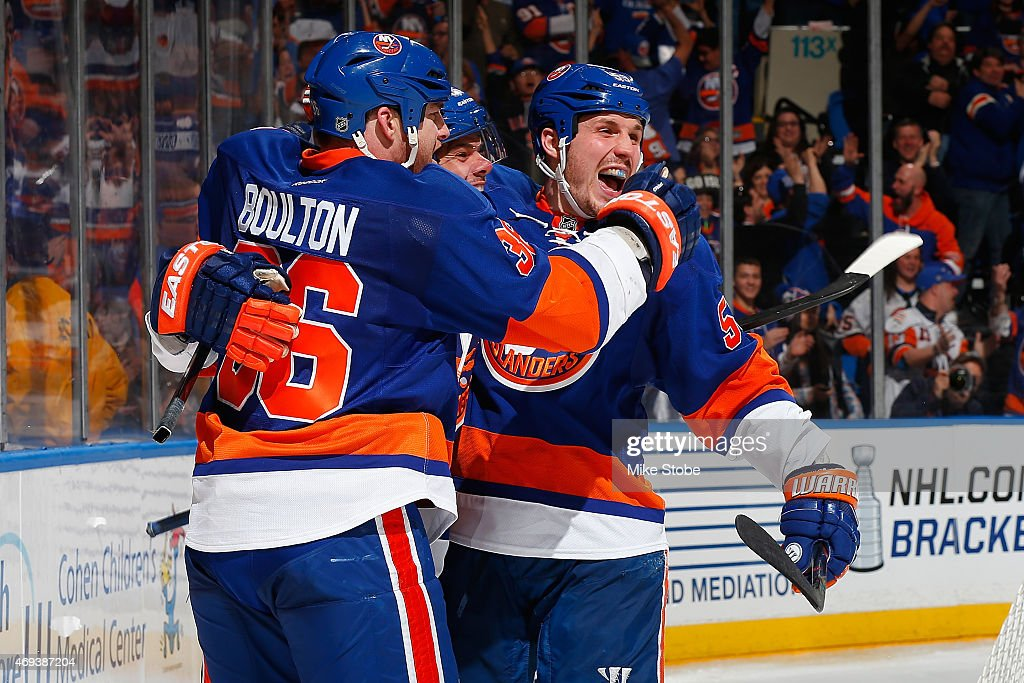 Eric Boulton #36 of the New York Islanders is congratulated by teammates Tyler Kennedy #26 and Casey Cizikas #53 after scoring a third period goal against the Columbus Blue Jackets at Nassau Veterans Memorial Coliseum on April 11, 2015 in Uniondale, New York.