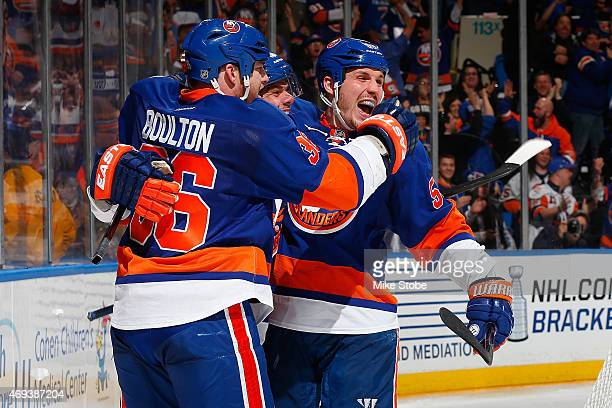 Eric Boulton of the New York Islanders is congratulated by teammates Tyler Kennedy and Casey Cizikas after scoring a third period goal against the...