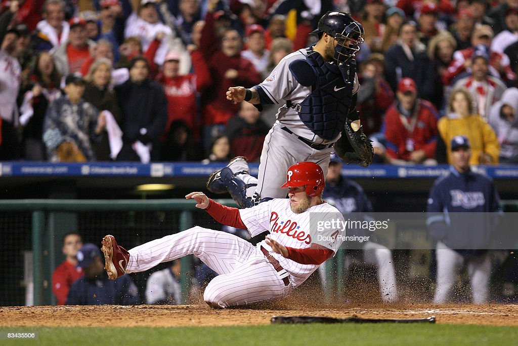 Eric Bruntlett #4 of the Philadelphia Phillies scores the winning run in front of Dioner Navarro #30 of the Tampa Bay Rays during game three of the 2008 MLB World Series on October 25, 2008 at Citizens Bank Park in Philadelphia, Pennsylvania.