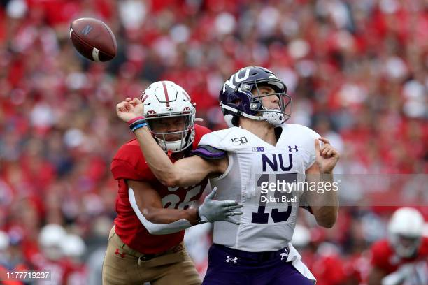 Eric Burrell of the Wisconsin Badgers forces a fumble against Hunter Johnson of the Northwestern Wildcats in the third quarter at Camp Randall...