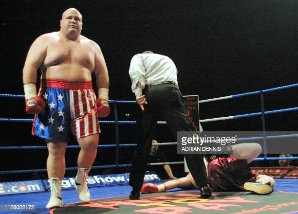 Eric Butterbean Esch walks away while the referee counts out Britain's Shane Woollas during the first round of their superheavyweight fight at...