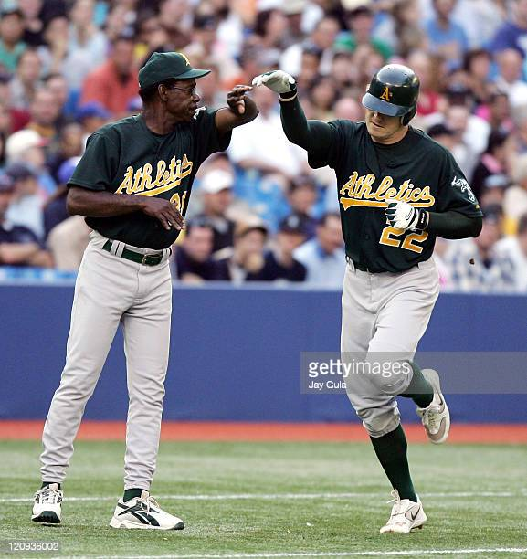 Eric Byrnes is congratulated by 3rd base coach Ron Washington after hitting a 2run home run in the 2nd inning to give the Oakland Athletics a 20 lead...