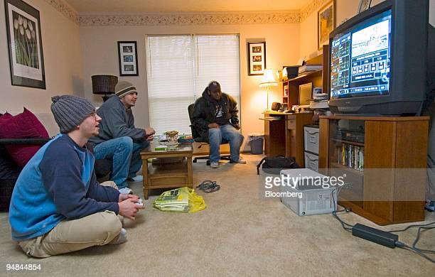Eric Cagnoli, left, his brother Phil Cagnoli, and friend Anokh Kondru, back, settle into a morning of game playing on Eric's Microsoft XBox 360 in...