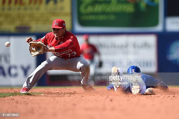Eric Campbell of the New York Mets beats a tag by Aledmys Diaz of the St Louis Cardinals during the fifth inning of a spring training game at...