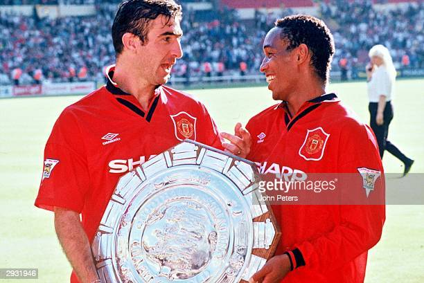 Eric Cantona and Paul Ince celebrate in the dressing room after the Arsenal v Manchester United Charity Shield match at Wembley Stadium London on...