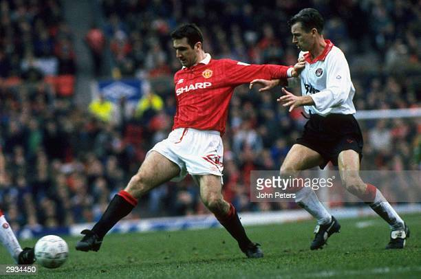Eric Cantona attempts to keep possession of the ball from two Charlton players during the game against Charlton Athletic in the sixth round of the...