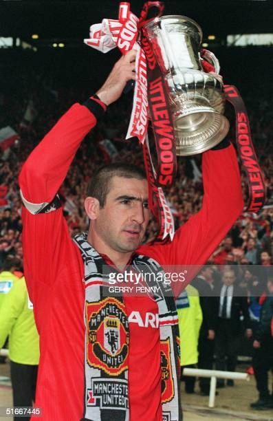 Eric Cantona holds the FA Cup 11 May 1996 at Wembley Stadium in London after he captained his team Manchester United to win the FA Cup Final against...