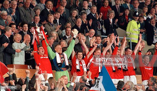 Eric Cantona of Manchester United with the trophy as his teammates celebrate after their 10 victory over Liverpool in the FA Cup Final at Wembley...