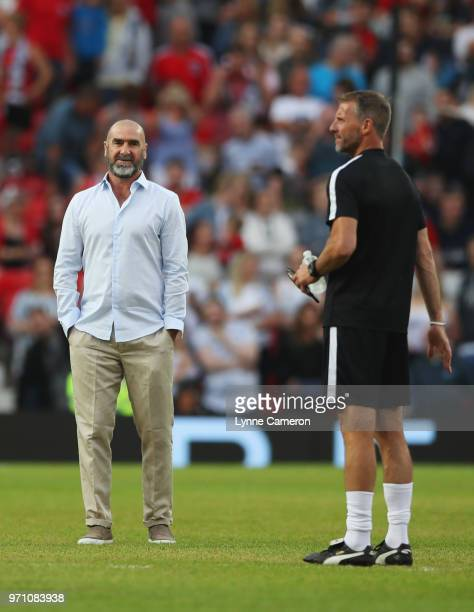 Eric Cantona of the Rest of the World and Mike Stowell goalkeeping coach of England look on prior to the Soccer Aid for UNICEF 2018 match between...