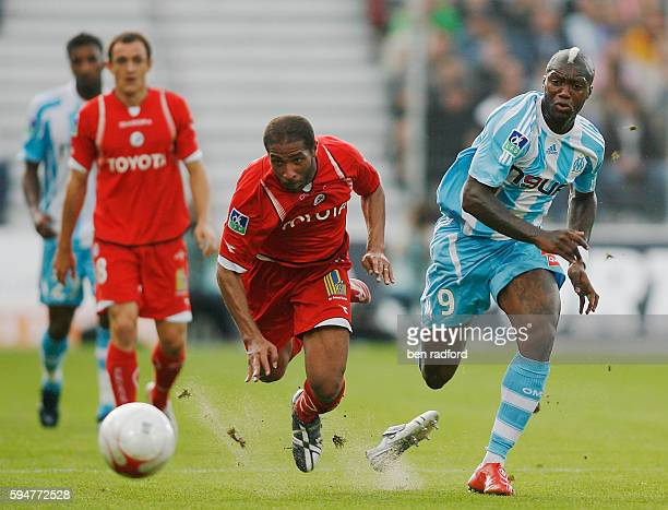 Eric Chelle of Valenciennes loses his football boot as Djibril Cisse of Marseille gives chase during the Ligue 1 match between Valenciennes and...