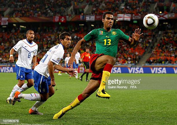 Eric Choupo Moting of Cameroon chases the ball as Giovanni Van Bronckhorst and Nigel De Jong of the Netherlands look on during the 2010 FIFA World...
