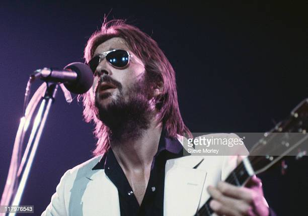 Eric Clapton, British guitarist, singing into a microphone and playing an acoustic guitar on stage during a live concert performance at the Nassau...