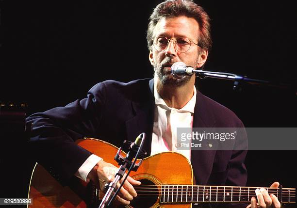 Eric Clapton performs on stage playing acoustic guitar at the Royal Albert Hall London 1998