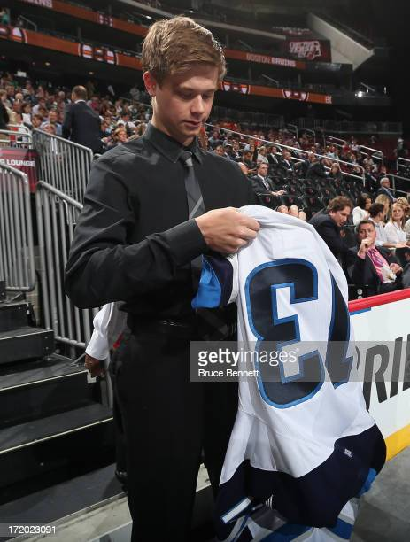 Eric Comrie drafted overall in the second round by the Winnipeg Jets tries on his new team jersey after he was drafted during the 2013 NHL Draft at...