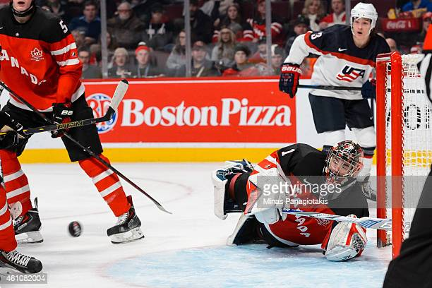 Eric Comrie of Team Canada slides across his goal crease as the puck approaches in a preliminary round game at the 2015 IIHF World Junior Hockey...