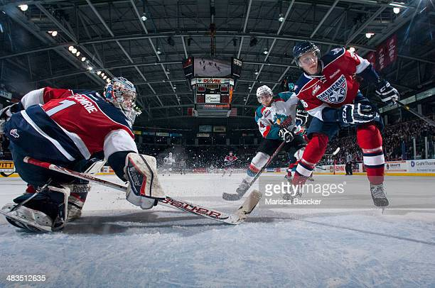 Eric Comrie of the TriCity Americans makes a save on a shot from Tyson Baillie of the Kelowna Rockets on March 22 2014 during game 1 of the first...