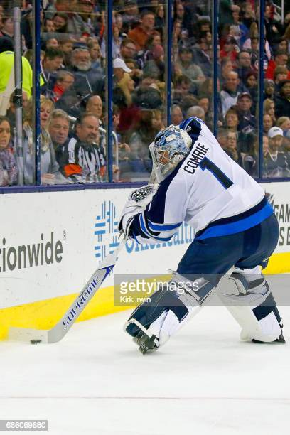 Eric Comrie of the Winnipeg Jets clears the puck while making his NHL debut during the game against the Columbus Blue Jackets on April 6 2017 at...