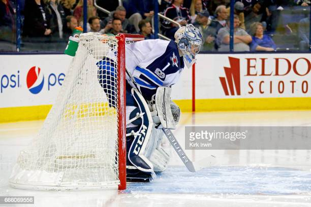 Eric Comrie of the Winnipeg Jets prepares for the start of the second period while making his NHL debut during the game against the Columbus Blue...