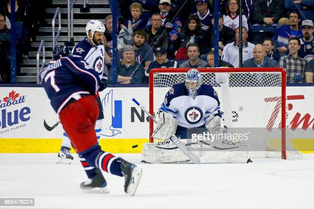 Eric Comrie of the Winnipeg Jets stops a shot by Jack Johnson of the Columbus Blue Jackets during the third period on April 6 2017 at Nationwide...