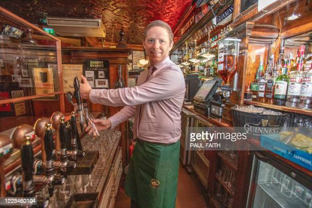 Eric Connell, manager of the Doheny & Nesbitt pub, serves a pint of beer to a customer in Dublin on June 29 as lockdown measures begin to be eased. -...