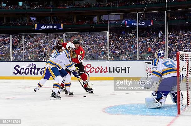 Eric Daze of the Chicago Blackhawks plays the puck between Al MacInnis and Chris Pronger of the St Louis Blues as goaltender Chris Mason of the St...
