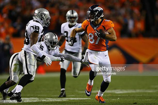 Eric Decker of the Denver Broncos carries the ball against Brandian Ross and DJ Hayden of the Oakland Raiders in the second quarter at Sports...