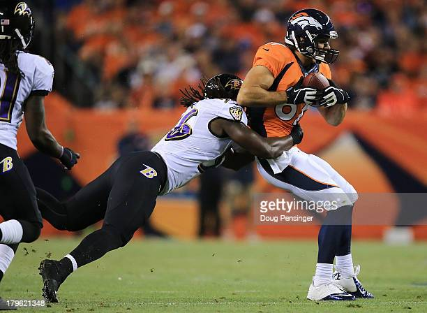 Eric Decker of the Denver Broncos catches a pass in front of Josh Bynes of the Baltimore Ravens in the first half during the game at Sports Authority...