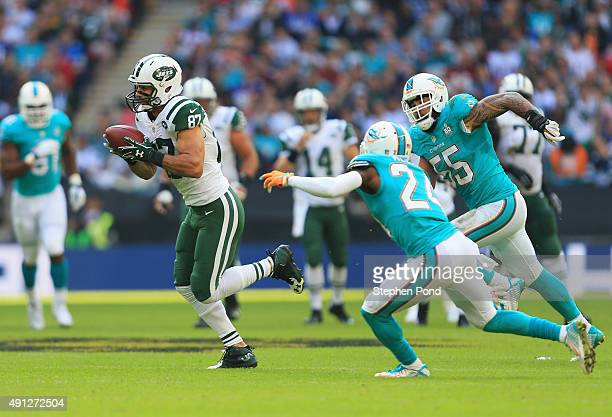 Eric Decker of the New York Jets evades Brice McCain of the Miami Dolphins and Koa Misi of the Miami Dolphins during the game at Wembley Stadium on...