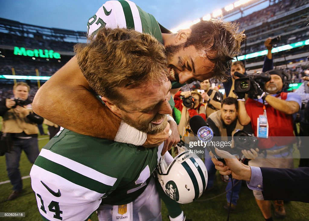 Eric Decker #87 of the New York Jets jumps on the back of Ryan Fitzpatrick #14 of the New York Jets during a television interview after their 26-20 overtime win against the New England Patriots at MetLife Stadium on December 27, 2015 in East Rutherford, New Jersey.