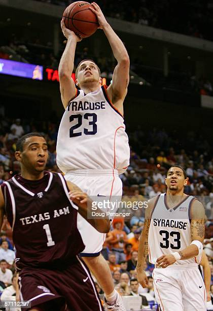 Eric Devendorf of the Syracuse Orange shoots over Acie Law of the Texas AM Aggies while teammate Terrence Roberts of the Orange looks on during round...