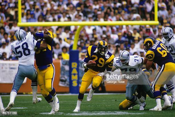 Eric Dickerson of the Los Angeles Rams eludes defensive end John Dutton of the Dallas Cowboys as he runs down field during the 1985 NFC Divisional...