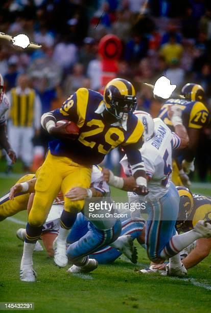Eric Dickerson of the Los Angeles Rams looks to break the tackle of Gregg Bingham of the Houston Oilers during an NFL football game December 9 1984...