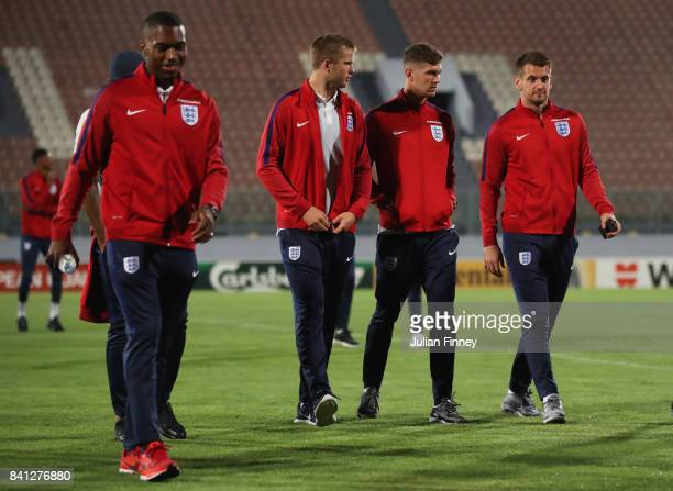 Eric Dier John Stones and Tom Heaton of England in discussion as they inspect the pitch on the eve of the World Cup qualifying match against Malta at...