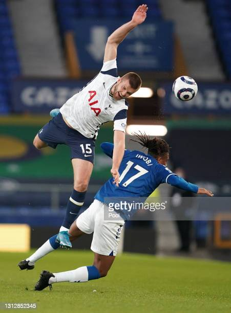 Eric Dier of Tottenham Hotspur is challenged by Alex Iwobi of Everton during the Premier League match between Everton and Tottenham Hotspur at...