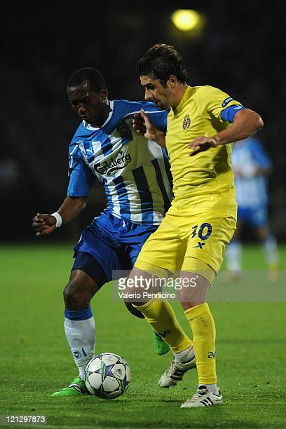 Eric Djemba-Djemba of OB Odense competes with Cani of Villarreal CF during the UEFA Champions League play-off first leg match between Odense BK and...