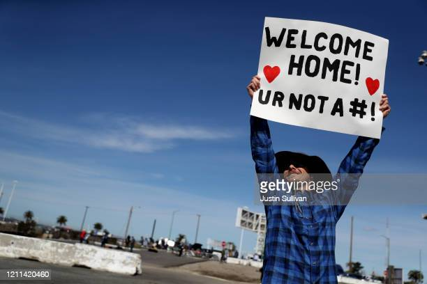 Eric Drake holds a sign as he watches the the Princess Cruises Grand Princess cruise ship dock at the port in Oakland CA on March 09 2020 in Oakland...