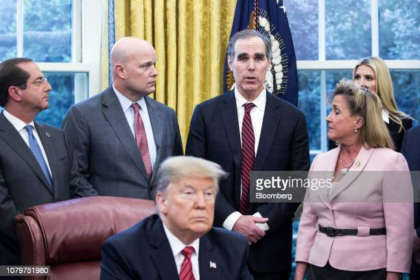 Eric Dreiband assistant US attorney general center right speaks Matthew Whitaker acting US attorney general center left listens during a signing...