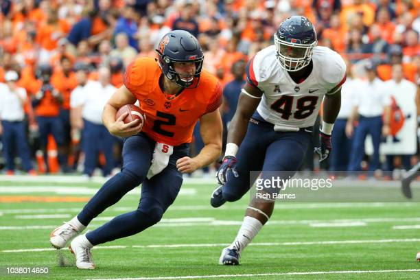 Kevin Mensah of the Connecticut Huskies runs with the ball as Antwan Cordy of the Syracuse Orange makes a diving tackle attempt during the second...