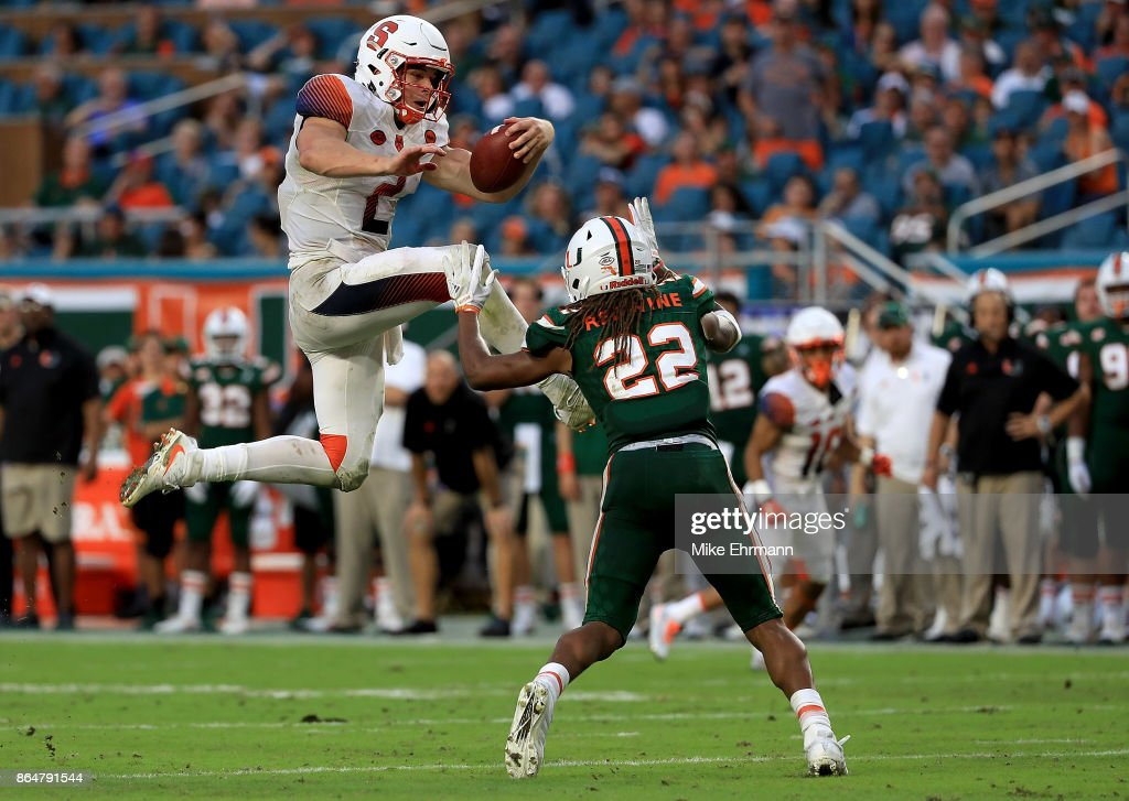 Eric Dungey #2 of the Syracuse Orange tries to jump over Sheldrick Redwine #22 of the Miami Hurricanes during a game at Sun Life Stadium on October 21, 2017 in Miami Gardens, Florida.