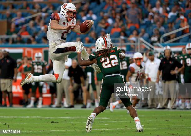 Eric Dungey of the Syracuse Orange tries to jump over Sheldrick Redwine of the Miami Hurricanes during a game at Sun Life Stadium on October 21 2017...