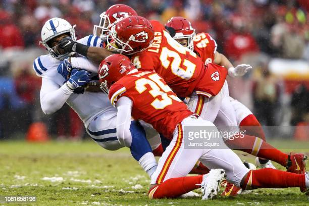 Eric Ebron of the Indianapolis Colts is tackled by Charvarius Ward and Jordan Lucas of the Kansas City Chiefs during the first quarter of the AFC...