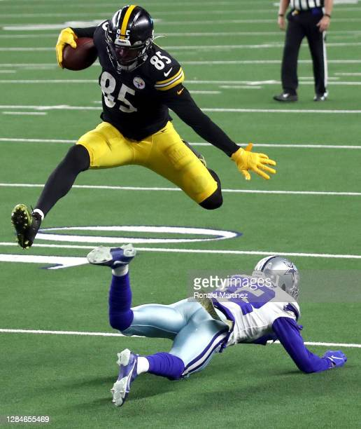Eric Ebron of the Pittsburgh Steelers leaps over Saivion Smith of the Dallas Cowboys during the second half at AT&T Stadium on November 08, 2020 in...