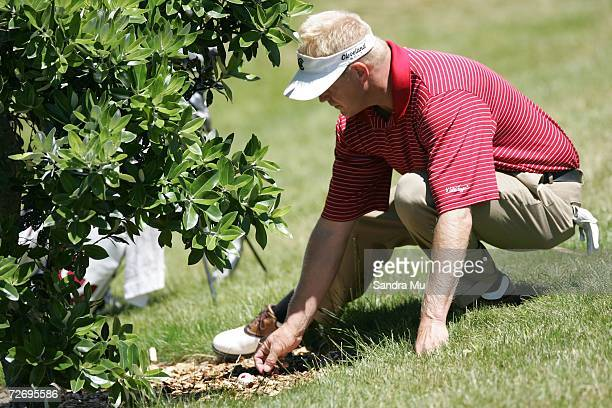 Eric Egloff of the U.S. Clears the space around the ball under a tree upon a hill on the 16th hole during round three of the New Zealand Open at Gulf...