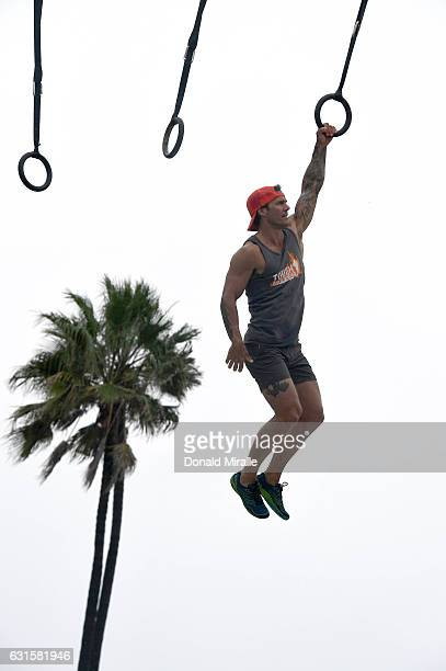 Eric 'ERock' Botsford certified Tough Mudder trainer swings from the 'Kong' obstacle during the Tough Mudder's 'Mudder Beach' Event which included...
