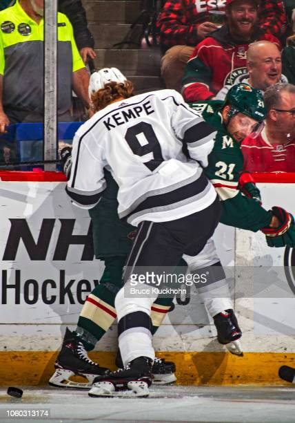 Eric Fehr of the Minnesota Wild and Adrian Kempe of the Los Angeles Kings battle for the puck along the boards during a game between the Minnesota...
