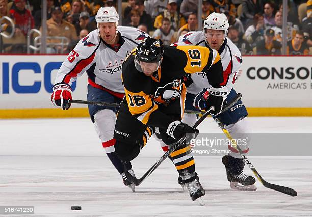 Eric Fehr of the Pittsburgh Penguins moves the puck up ice in front of Justin Williams and Jason Chimera of the Washington Capitals at Consol Energy...