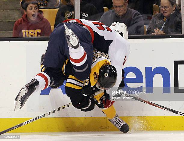 Eric Fehr of the Washington Capitals flips over Johnny Boychuk of the Boston Bruins at the TD Garden on October 21 2010 in Boston Massachusetts